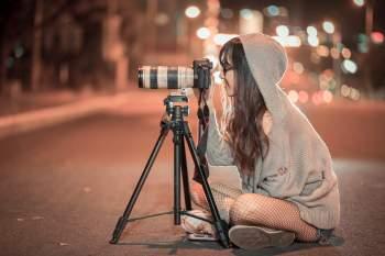 Eine Fotografin sitzt vor ihrer Kamera